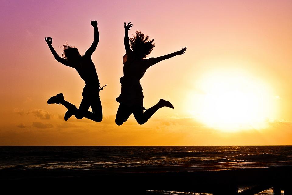 Twee vrouwen springen gelukkig in de lucht